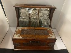 AN ORNATELY DECORATED AND ENGRAVED OAK ARTS AND CRAFTS STYLE TANTALUS/GAMING CABINET WITH THREE