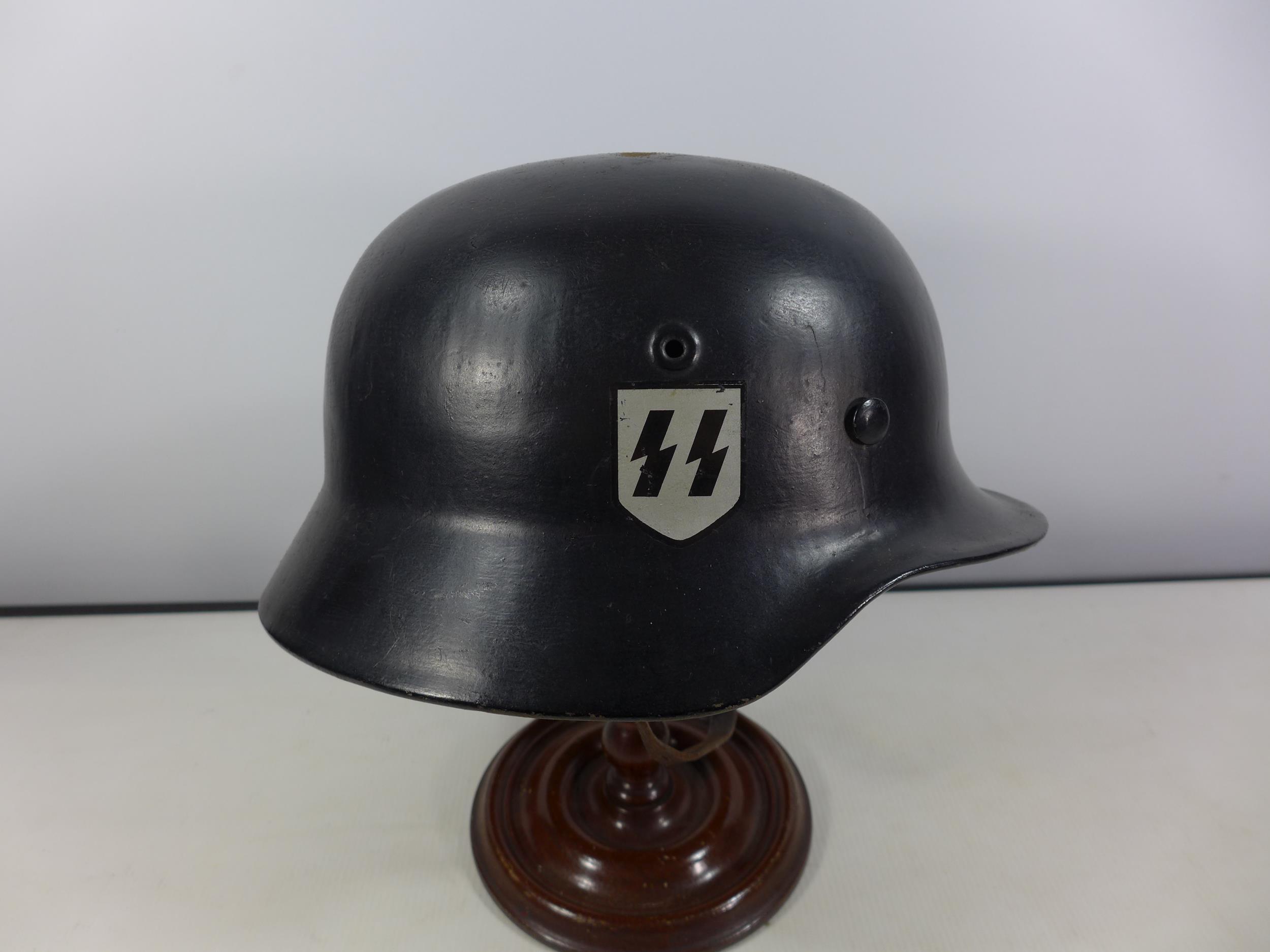 A GERMAN BLACK PAINTED METAL HELMET WITH SS RUNES AND SWASTIKA DECALS