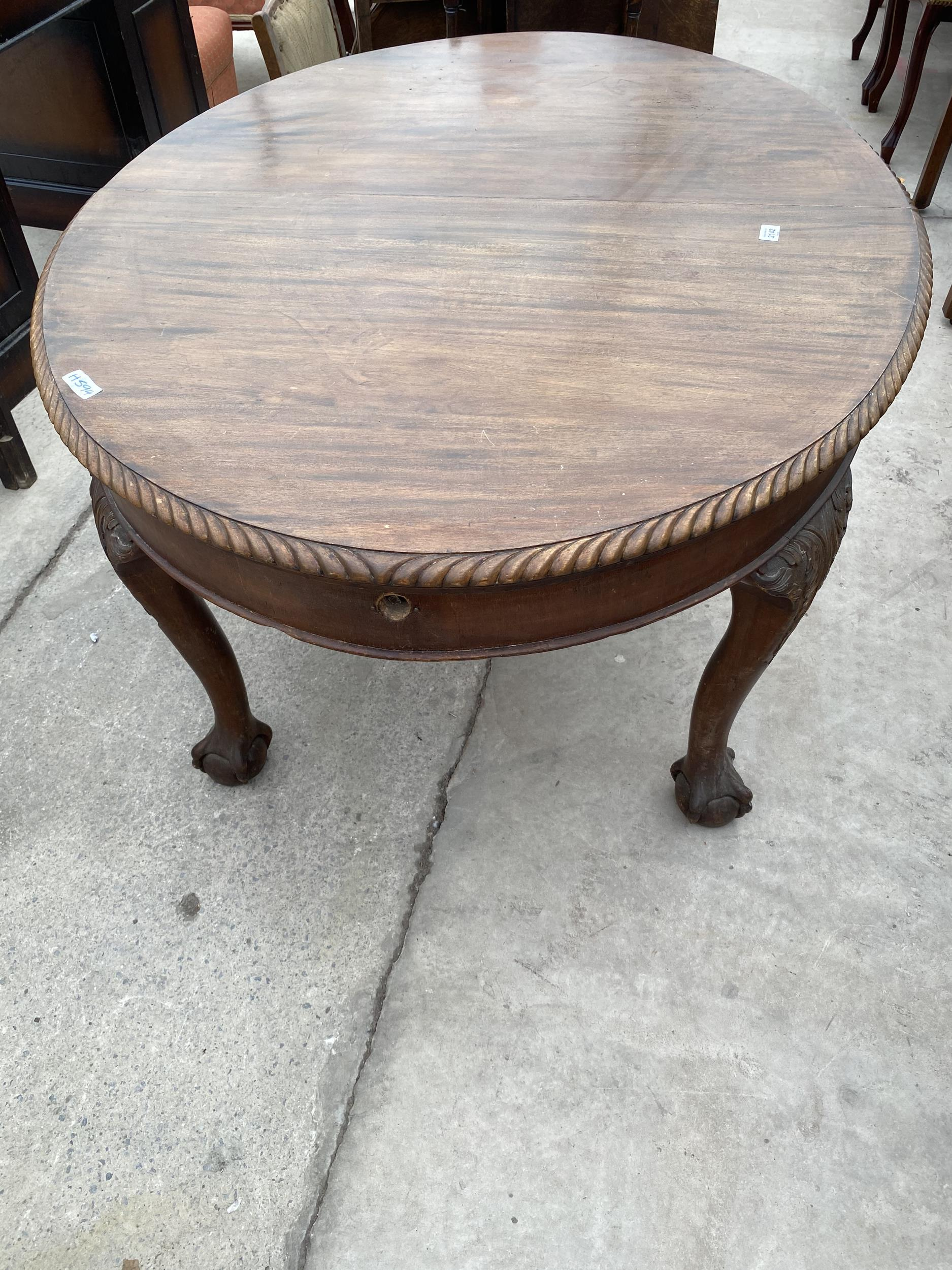 """AN EDWARDIAN MAHOGANY OVAL WIND-OUT DINING TABLE, 53 X 41"""", WITH ROPE EDGE, ON CABRIOLE LEGS, WITH"""