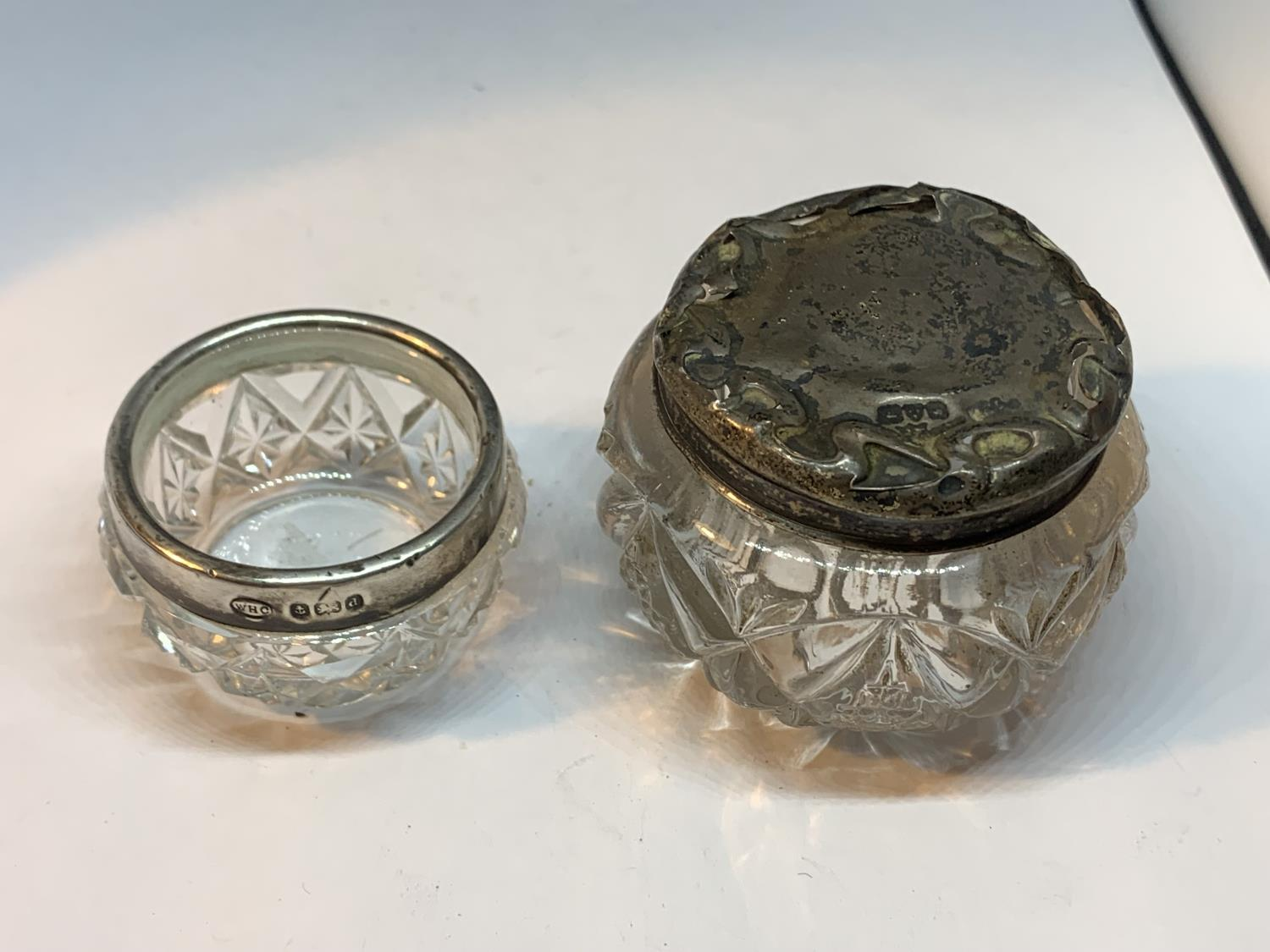 TWO GLASS POTS ONE WITH A HALLMARKED BIRMINGHAM SILVER RIM AND ONE WITH AN INDISTINCT HALLMARKED