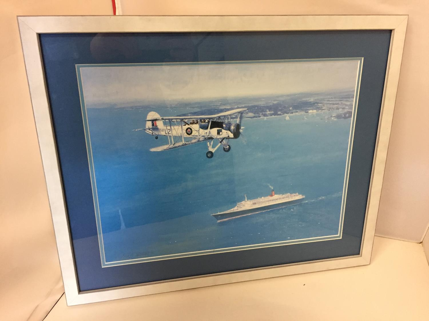 A FRAMED COLOURED PICTURE OF A SWORDFISH PLANE FLYING OVER A CRUISE SHIP 30CM X 40CM