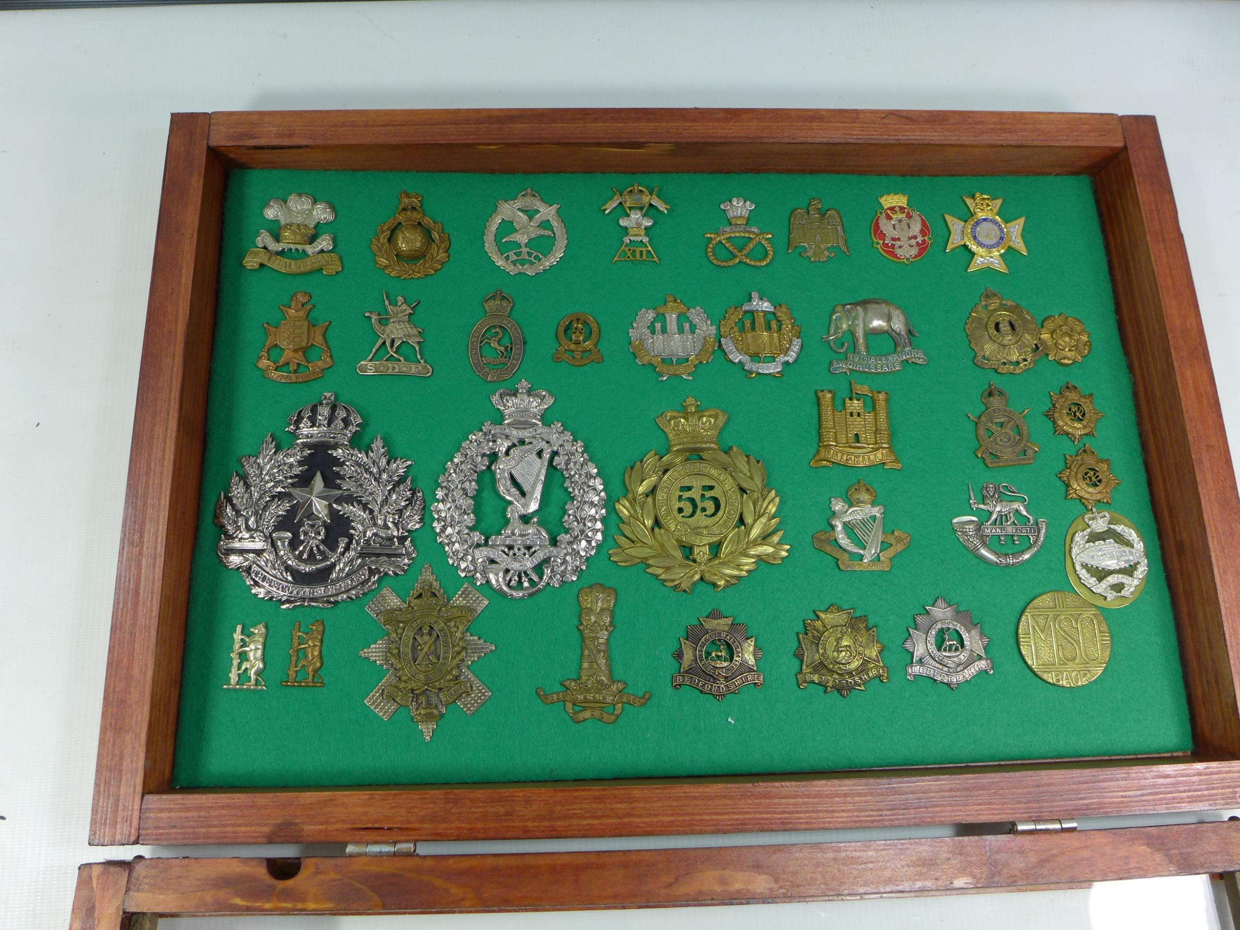 A GLAZED DISPLAY CASE CONTAINING THIRTY FIVE BRITISH MILITARY BADGES, 33CM X 49CM