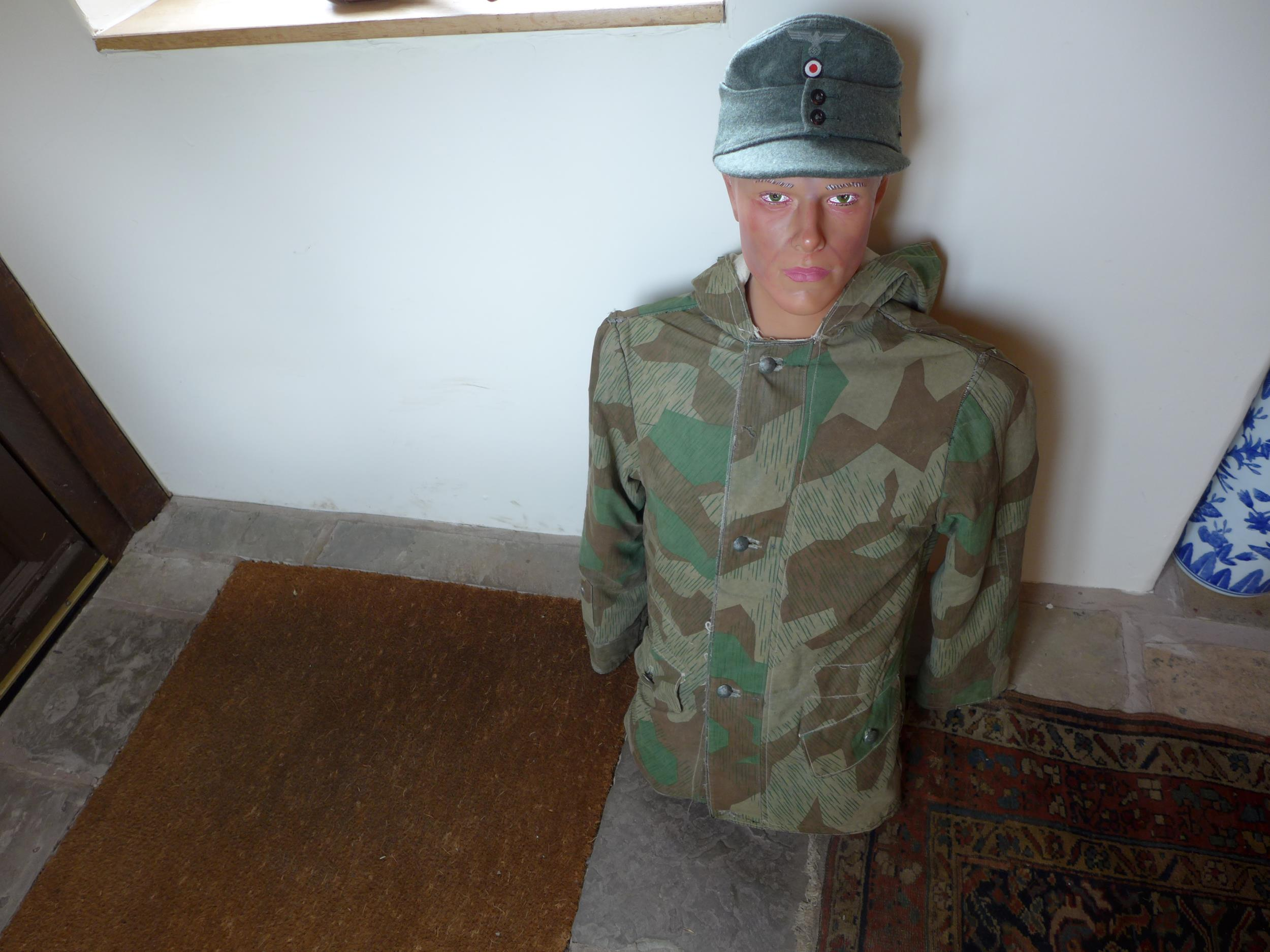 A MALE MANEQUIN WEARING A GERMAN FIELD CAP AND CAMOUFLAGE COAT