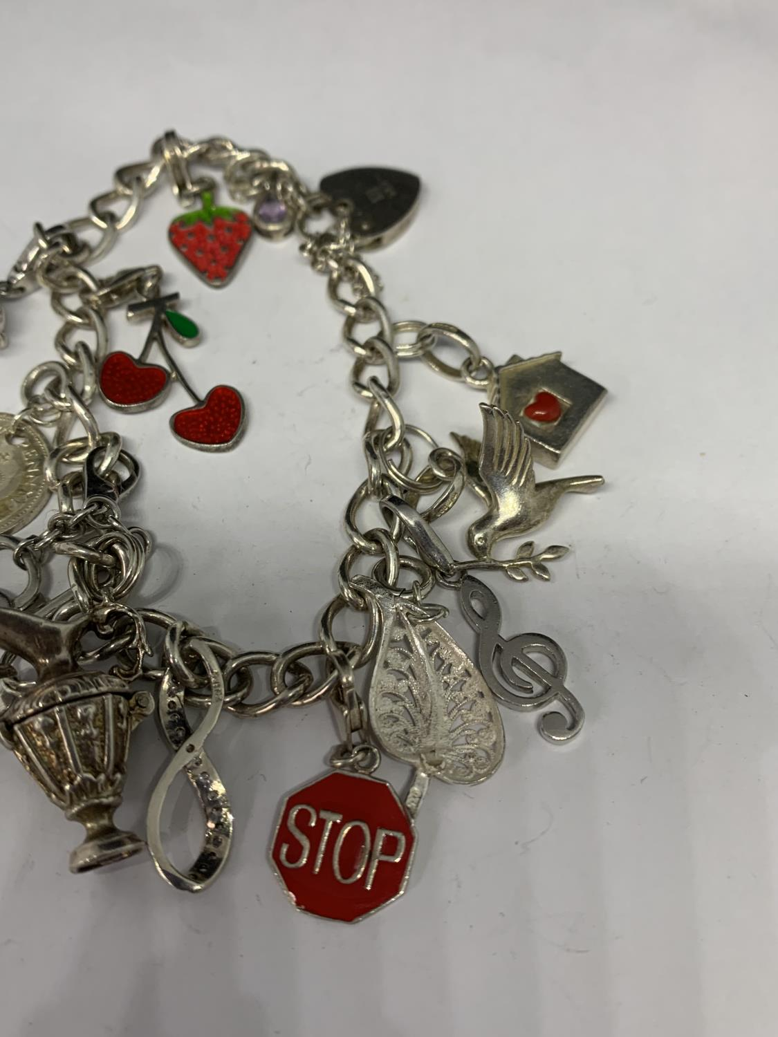 A HEAVY SILVER CHARM BRACELET WITH THIRTEEN CHARMS TO INCLUDE A STRAWBERRY, CHERRIES, DOVE ETC - Image 4 of 4