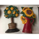 TWO CAST IRON DOOR STOPS TO INCLUDE AN ORANGE TREE AND A SUNFLOWER DESIGN