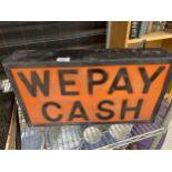 AN ILLUMINATED 'WE PAY CASH' SIGN