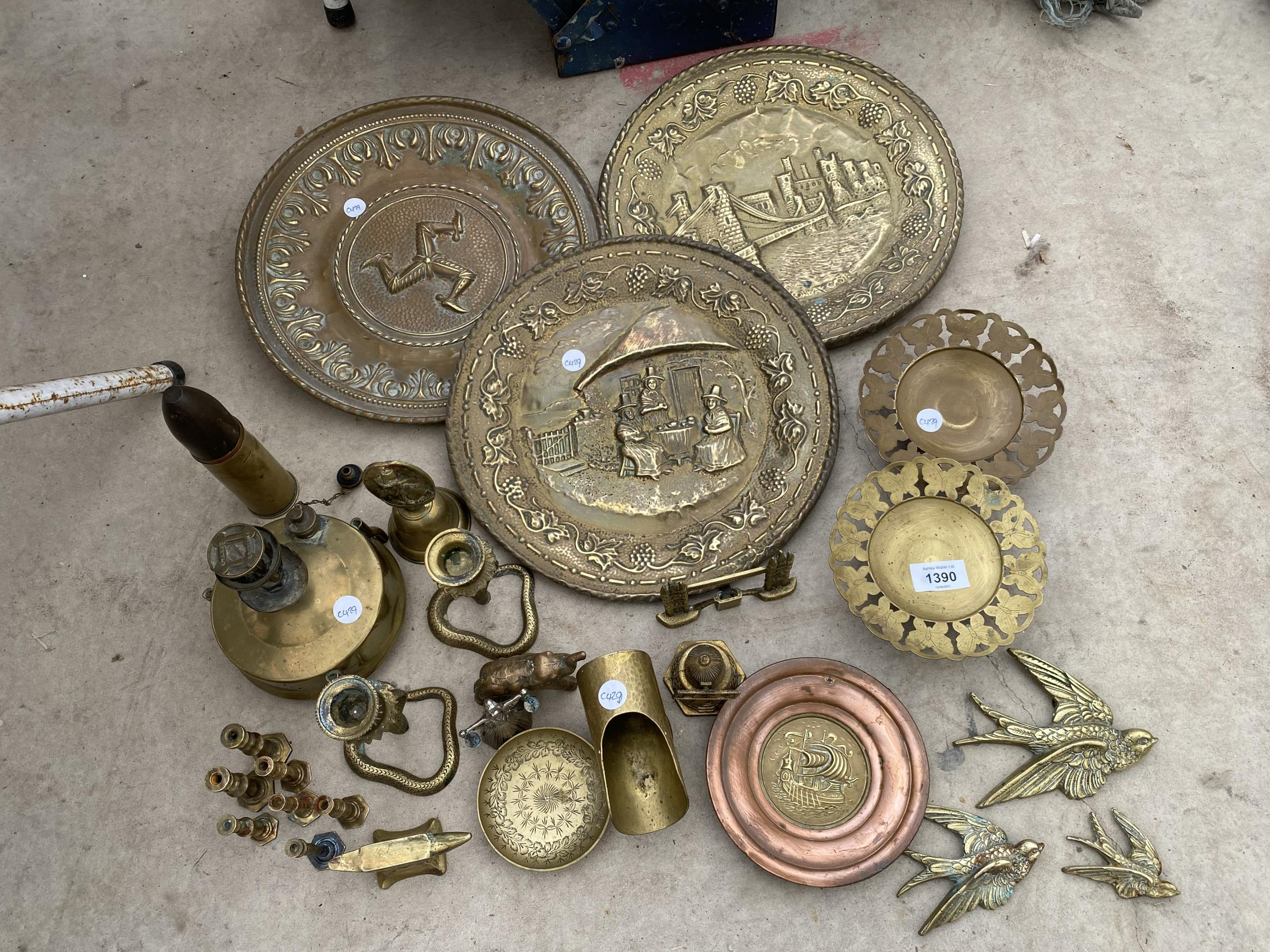AN ASSORTMENT OF BRASS TO INCLUDE BRASS PLAQUES, CANDLE HOLDERS AND AN OIL LAMP ETC