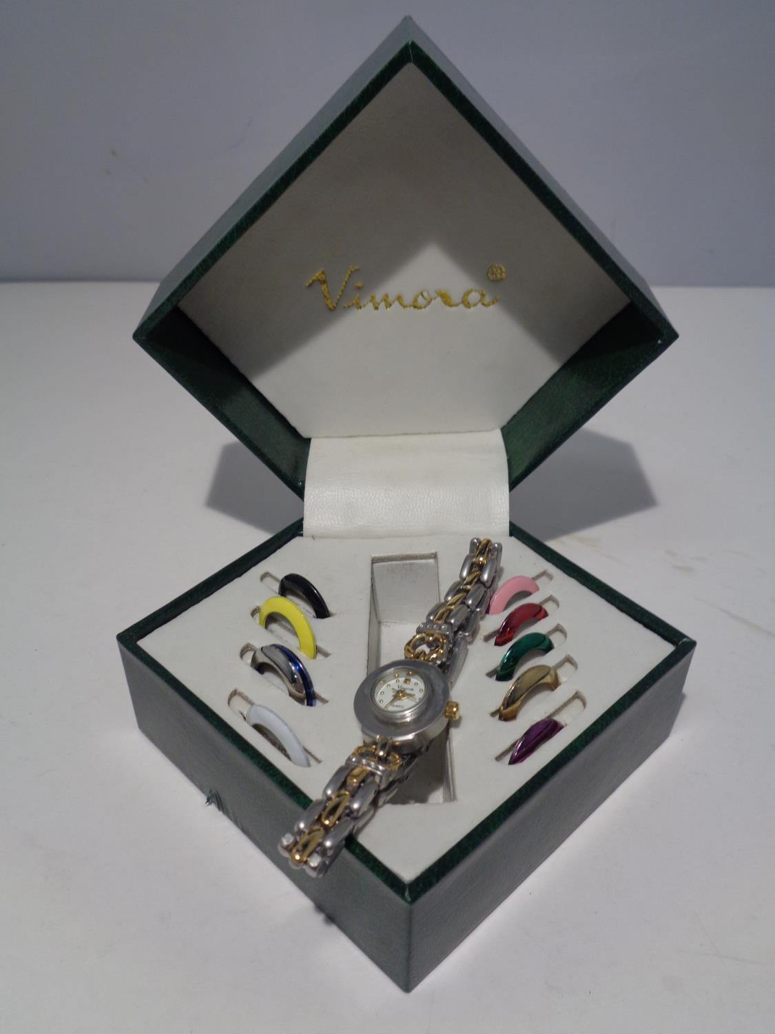 A VIMORA BOXED WATCH WITH COLOURED INTERCHANGEABLE WATCH FACE SURROUNDINGS