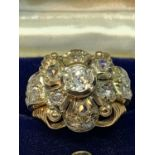 AN 18 CARAT WHITE AND YELLOW GOLD ART DECO CLUSTER RING WITH A CENTRE DIAMOND, SIX SURROUNDING