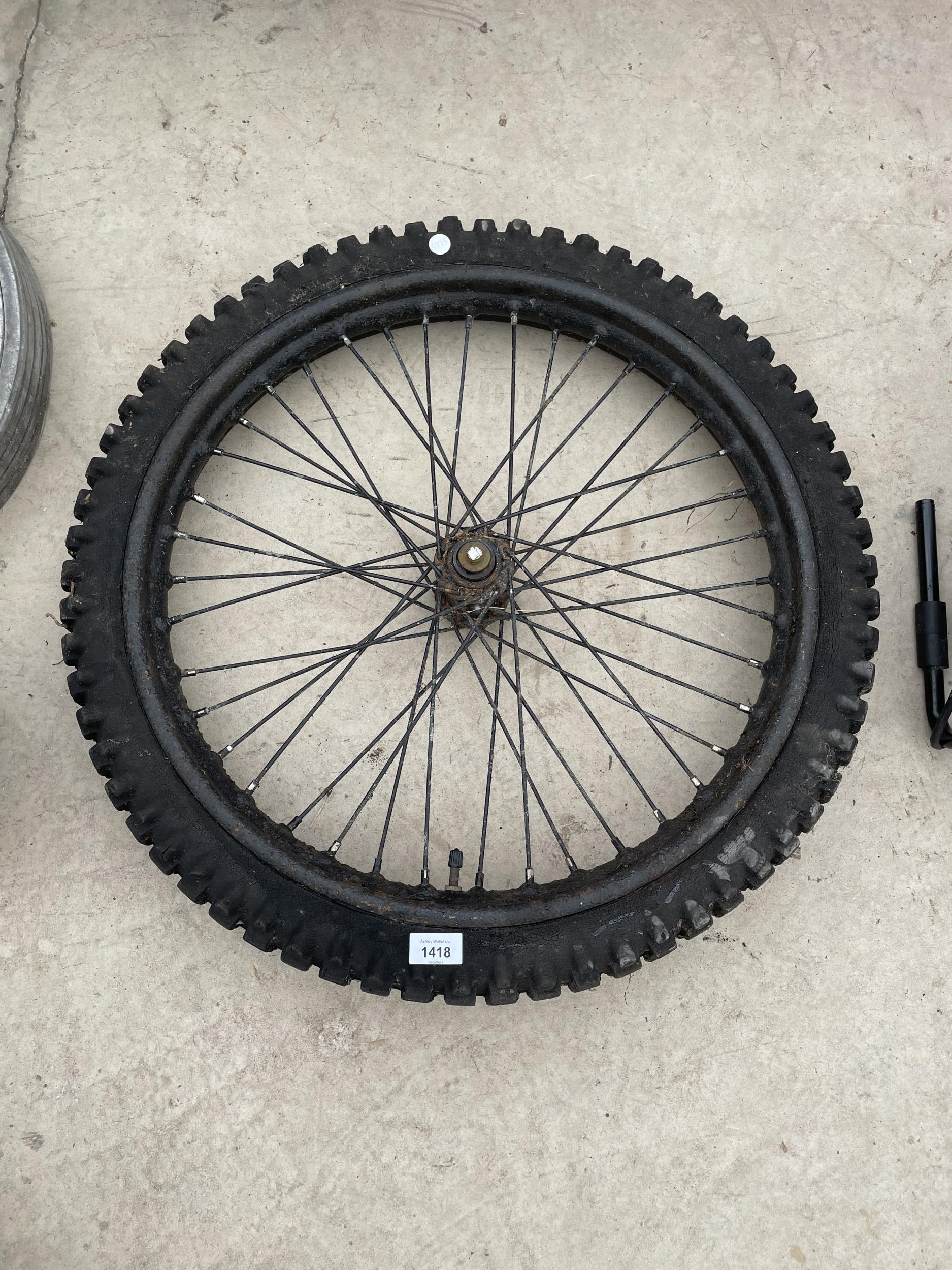 A LARGE THICK TREAD SIDE CAR WHEEL