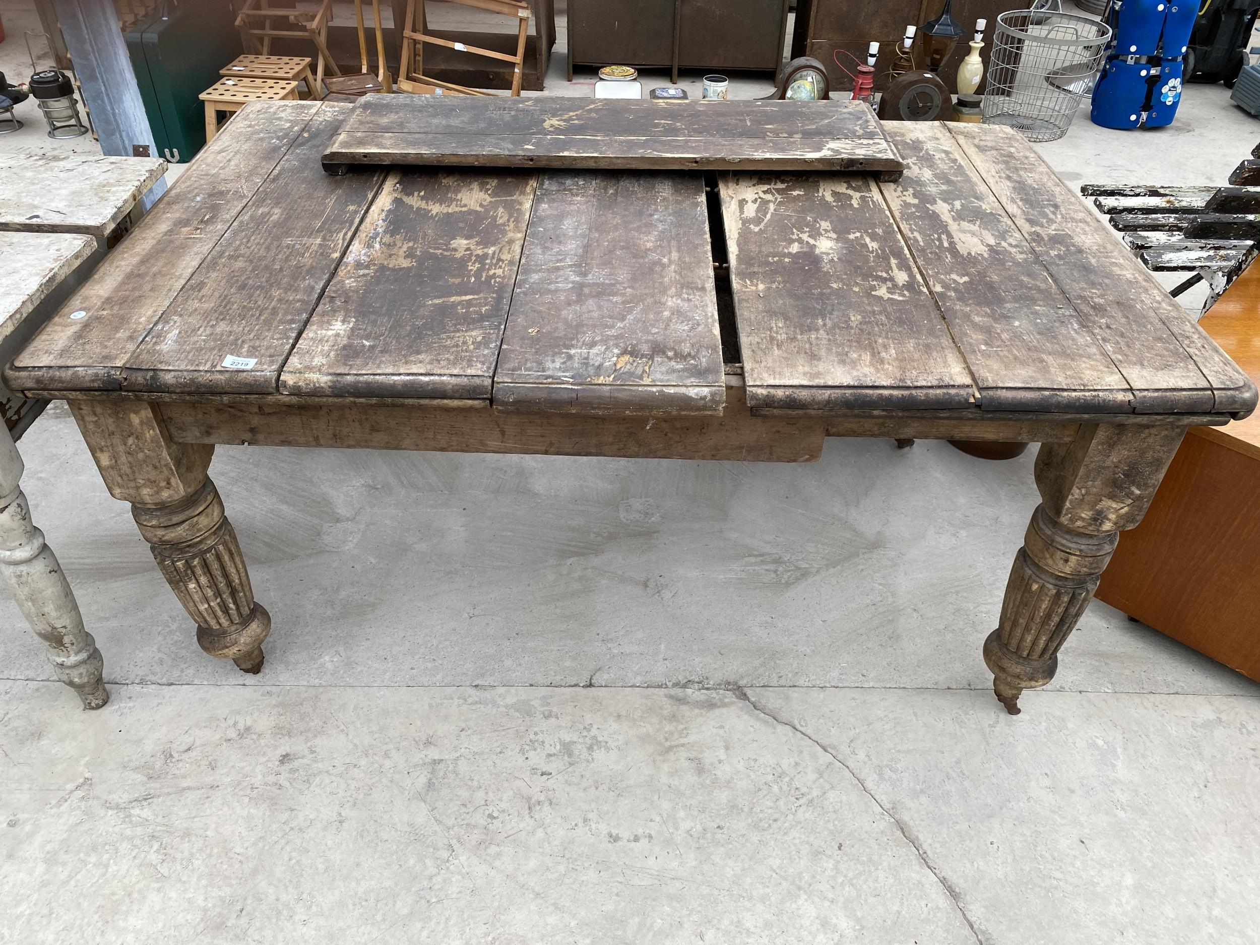 A VICTORIAN SCRUB-TOP WIND OUT DINING TABLE ON TURNED AND FLUTED LEGS