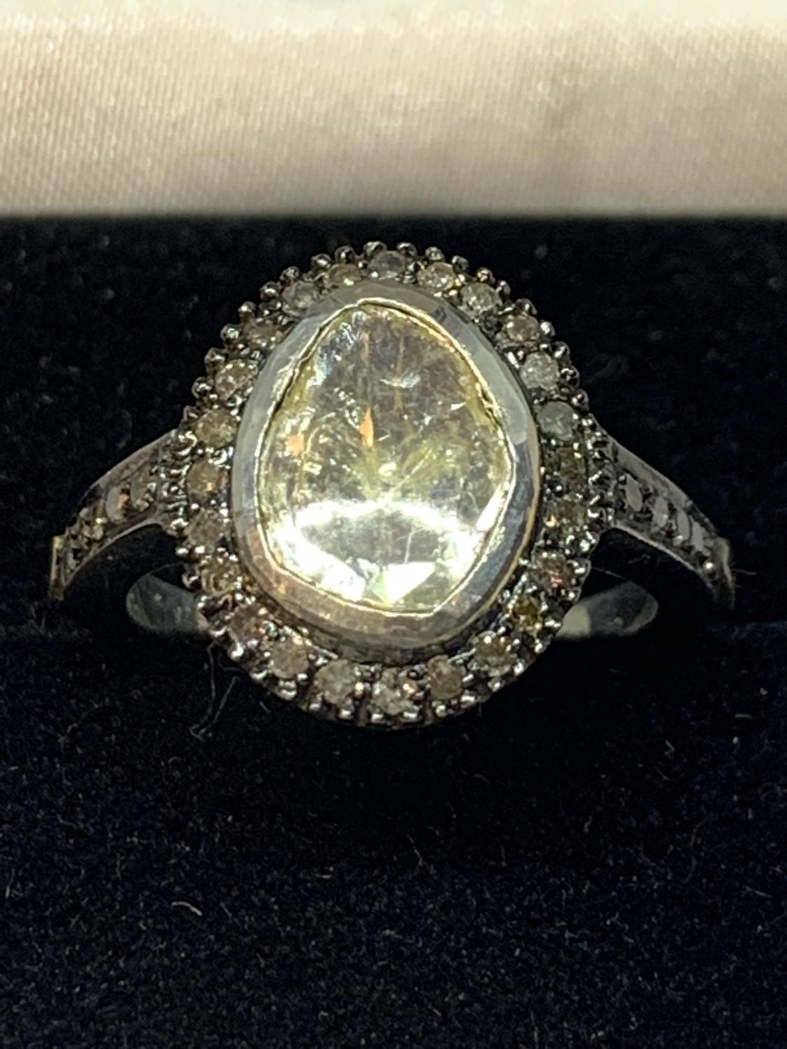 A CONTINENTAL WHITE AND YELLOW METAL RING WITH CENTRE DIAMOND AND SMALLER SURROUNDING DIAMONDS WHICH