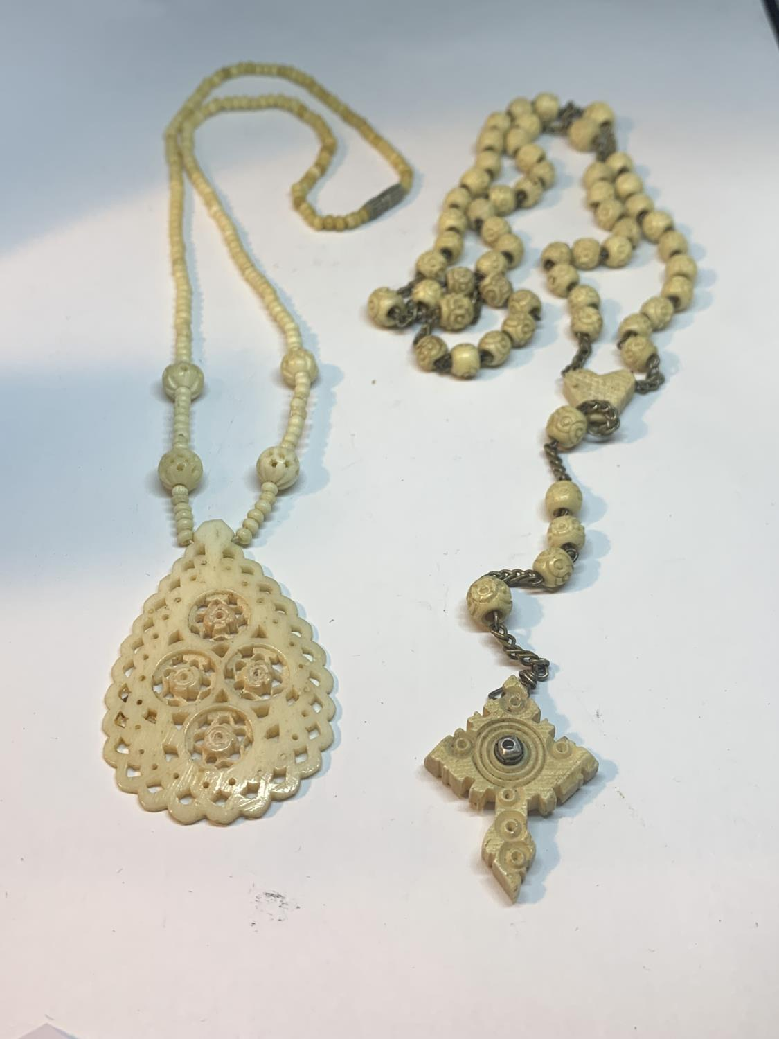 TWO CARVED BONE NECKLACES ONE WITH LARGE FOB AND ONE WITH A CROSS DESIGN