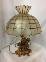 AN ORNATE GILDED LAMP BASE DEPICTING CHERUBS WITH A CAPIZ SHELL SHADE