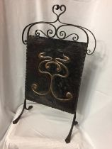 AN ARTS AND CRAFTS FIRE SCREEN WITH A DECORATIVE COPPER PANEL ON A WROUGHT IRON FRAME