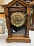 A VINTAGE AMERICAN WOODEN CASE CLOCK WITH A FRONT OPENING FACE
