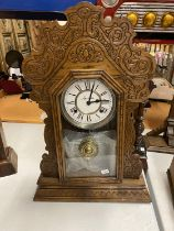 A VINTAGE GINGERBREAD CLOCK IN A CARVED WOODEN CASE WITH FRONT OPENING