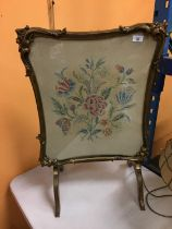 AN ORNATELY FRAMED CROSS STITCHED FIRE SCREEN WITH A FLOWER DESIGN