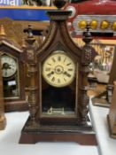 A VINTAGE AMERICAN CLOCK IN A GOTHIC STYLE WOODEN CASE