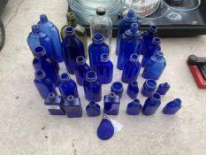 AN ASSORTMENT OF VARIOUS BLUE GLASS BOTTLES
