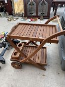 A TEAK TWO TIERED TROLLEY WITH REMOVABLE TRAY AND LOWER BOTTLE HOLDER