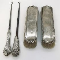 Two silver handled boot pulls along with two silver backed brushes