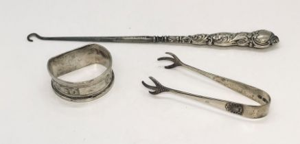 A collection of three silver items comprising of sugar tongs, button hook and napkin ring