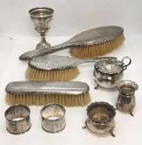 A collection of silver items including brushes, serviette rings, salt and pepper etc.