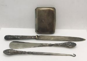 A hallmarked silver cigarette case along with three silver handled items