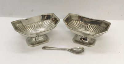 A pair of silver salts with one spoon