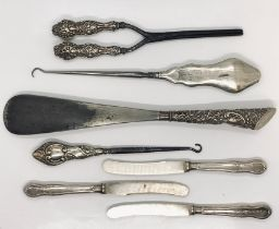 A collection of silver handled items including shoe horn, tongs, button hooks etc.