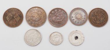 Sieben chinesische Münzen und ein Jeton