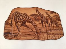 A pyrography scene on leather of giraffes by Hendrick Vrey. 2001