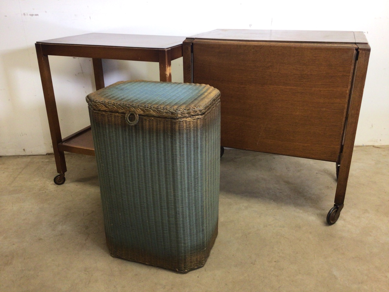 Lloyd loom lusty laundry basket also with two mid century tea trolleys one with folding drop flap