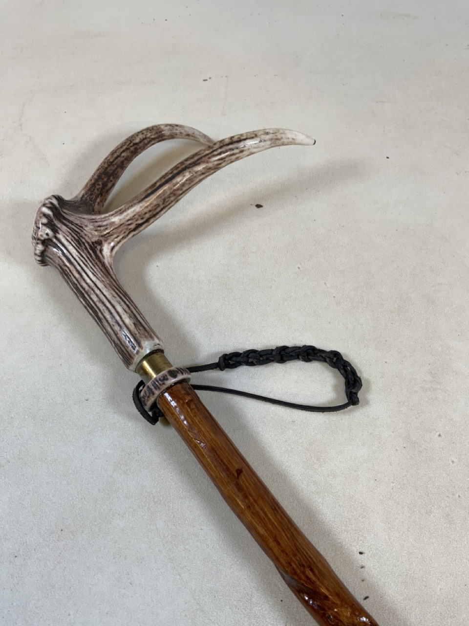 A walking stick - hazel with honeysuckle twist with a polished red deer antler handle with brass
