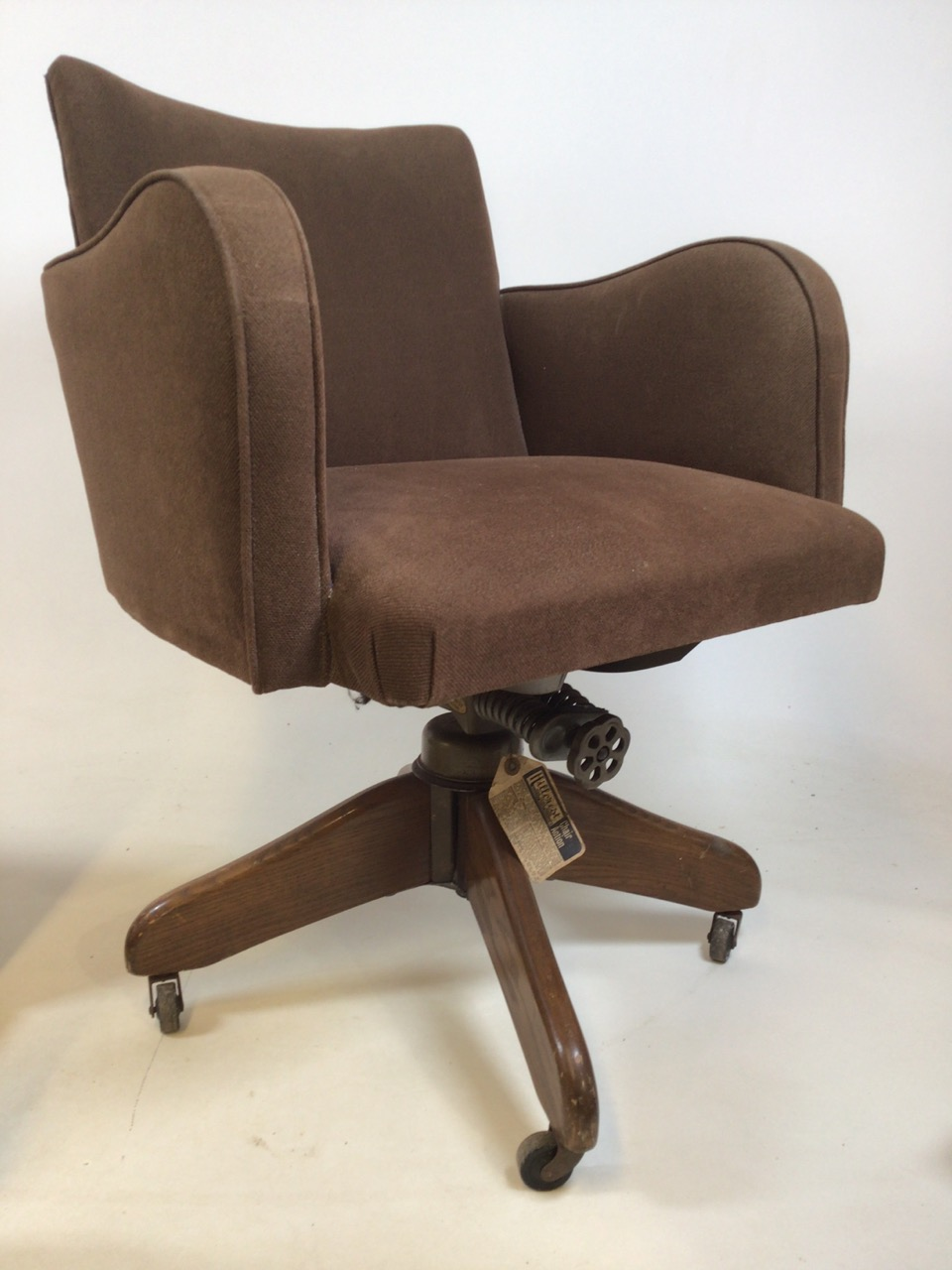 A Hillcrest mid century swivel office chair with Hillcrest label to metal base on oak stand with