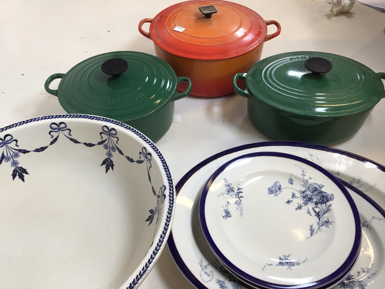 Le Creuset casserole dishes orange and green, Worcester blue and white plates also with a blue and