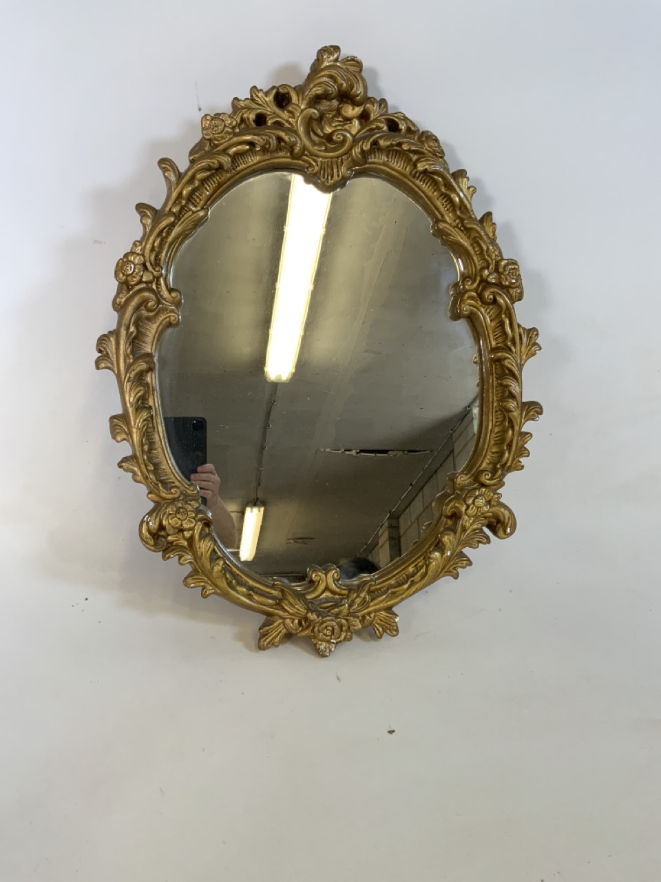 A gilt framed oval Rocco style mirror . W:51cm x H:64cm