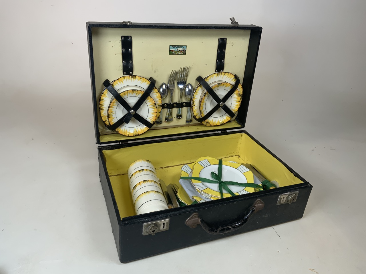 An early Brexton picnic hamper with four place settings in wooden box with yellow interior. Original