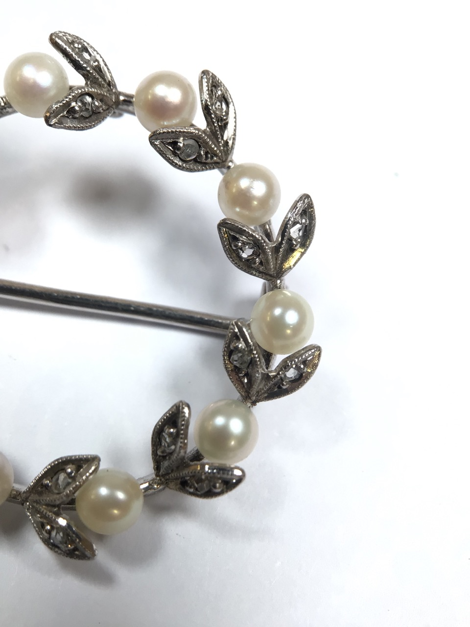An unmarked precious white metal Belle Époque wreath brooch set with a surround of pearls and - Image 3 of 7
