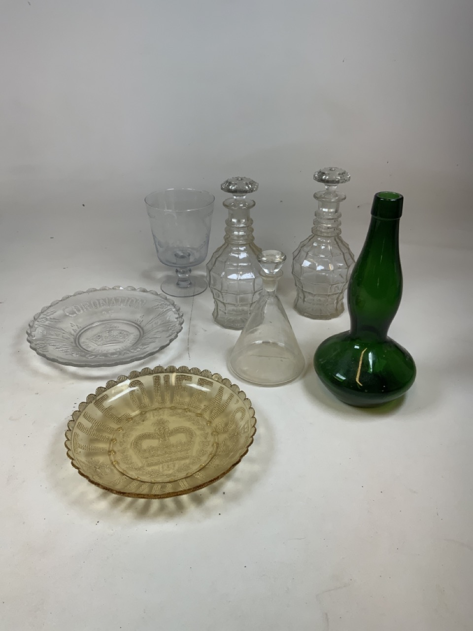 A pair of moulded glass decanters Height 27cm together with a ships decanter 20cm height, a green