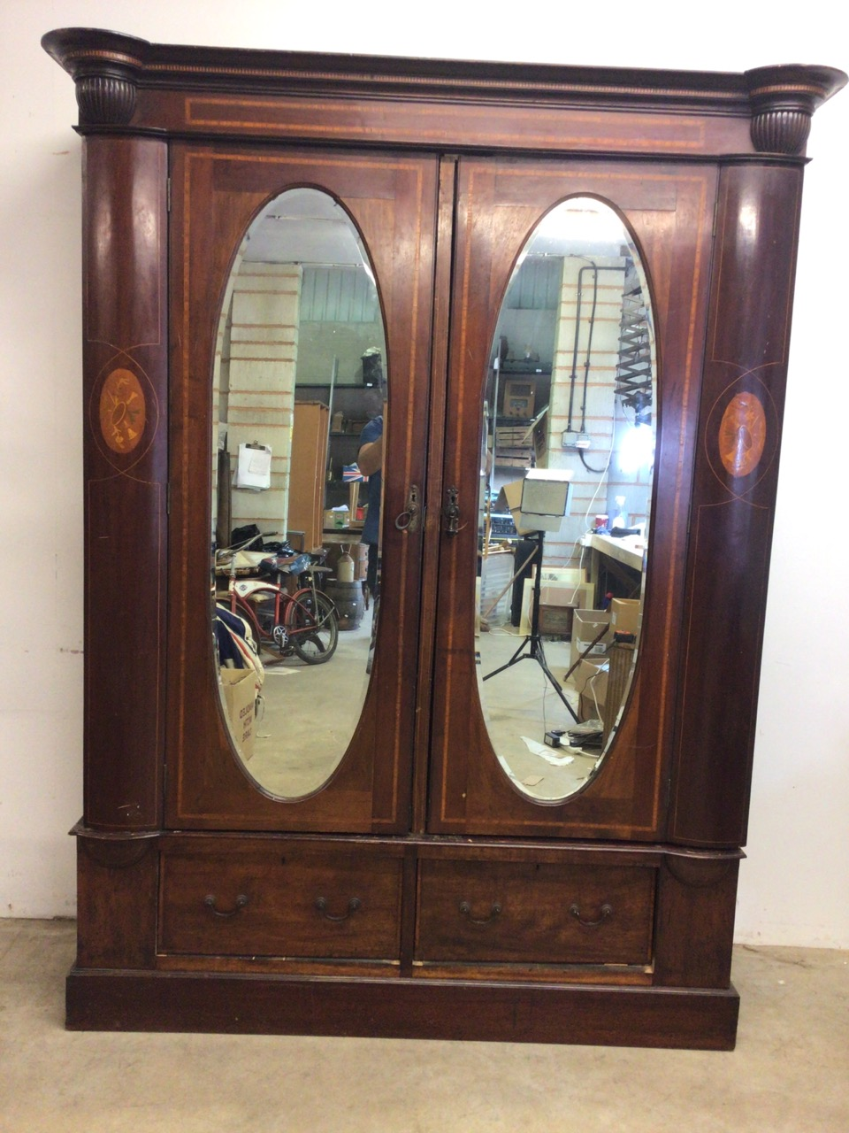 An mahogany Edwardian inlaid double wardrobe with oval bevelled mirrored doors two drawers to