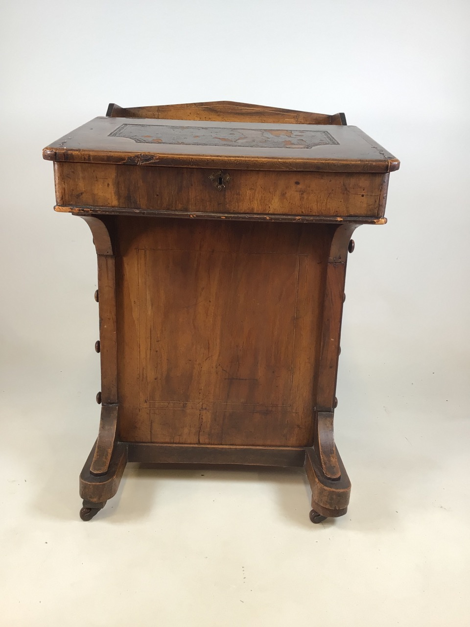 A Victorian inlaid davenport on ceramic castors with leather writing slope to interior desk. With