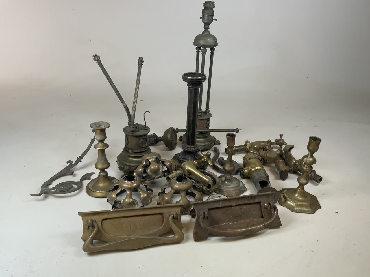 A large quantity of brass and copper items including taps, door knockers, lamps and candle sticks
