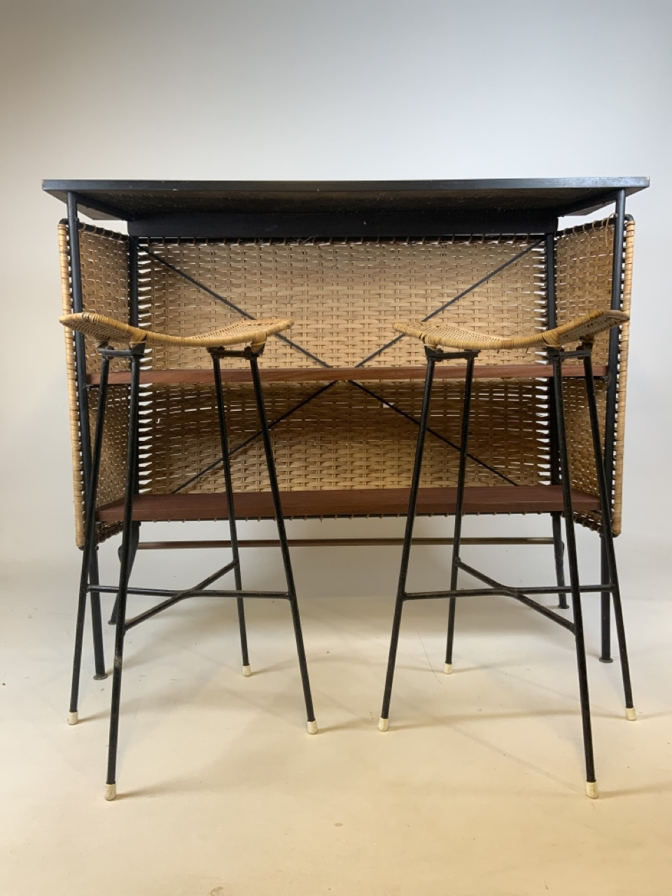 A Franco Albini mid century wicker and iron bar and two bar stools. Bar has two teak shelves to