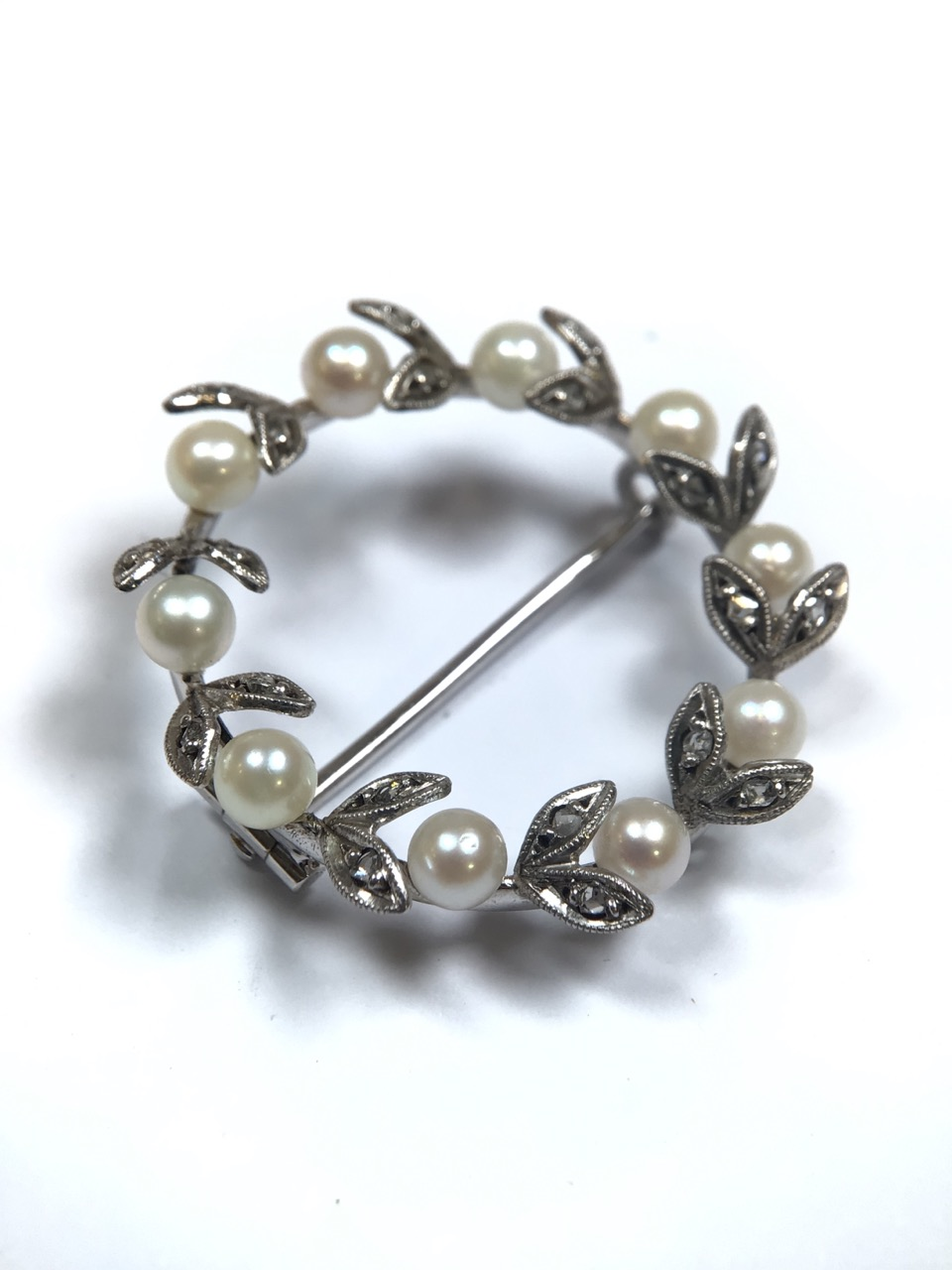 An unmarked precious white metal Belle Époque wreath brooch set with a surround of pearls and