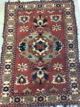 A Persian Hamadan rug with terracotta ground surrounded by a large cream border. W:173cm x H:120cm