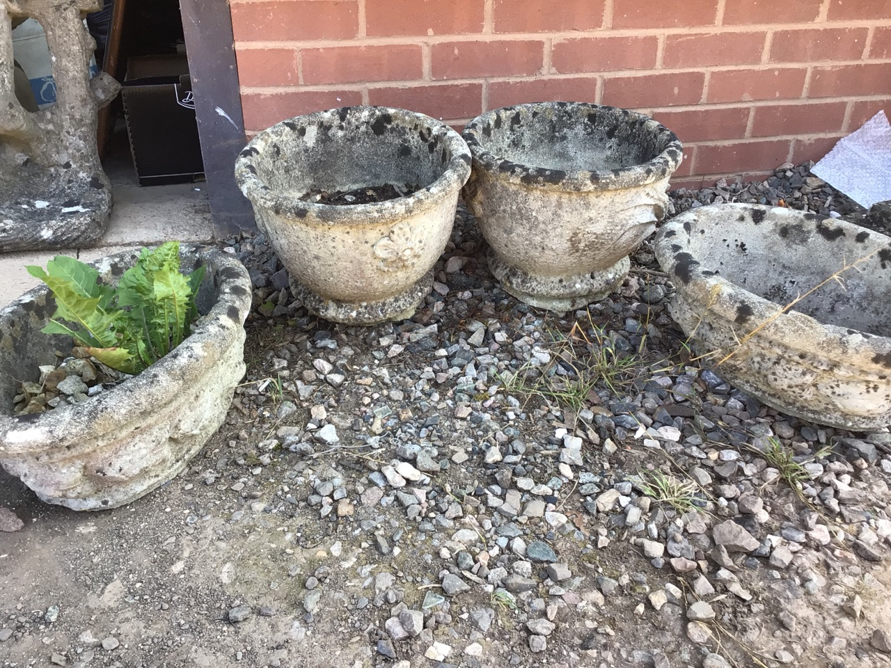 Four decorative concrete planters two circular and two oval. W:34cm x D:34cm x H:24cm