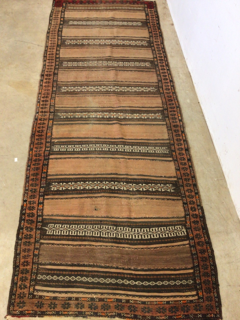 An antique eastern runner with Aztec influence. W:290cm x H:105cm