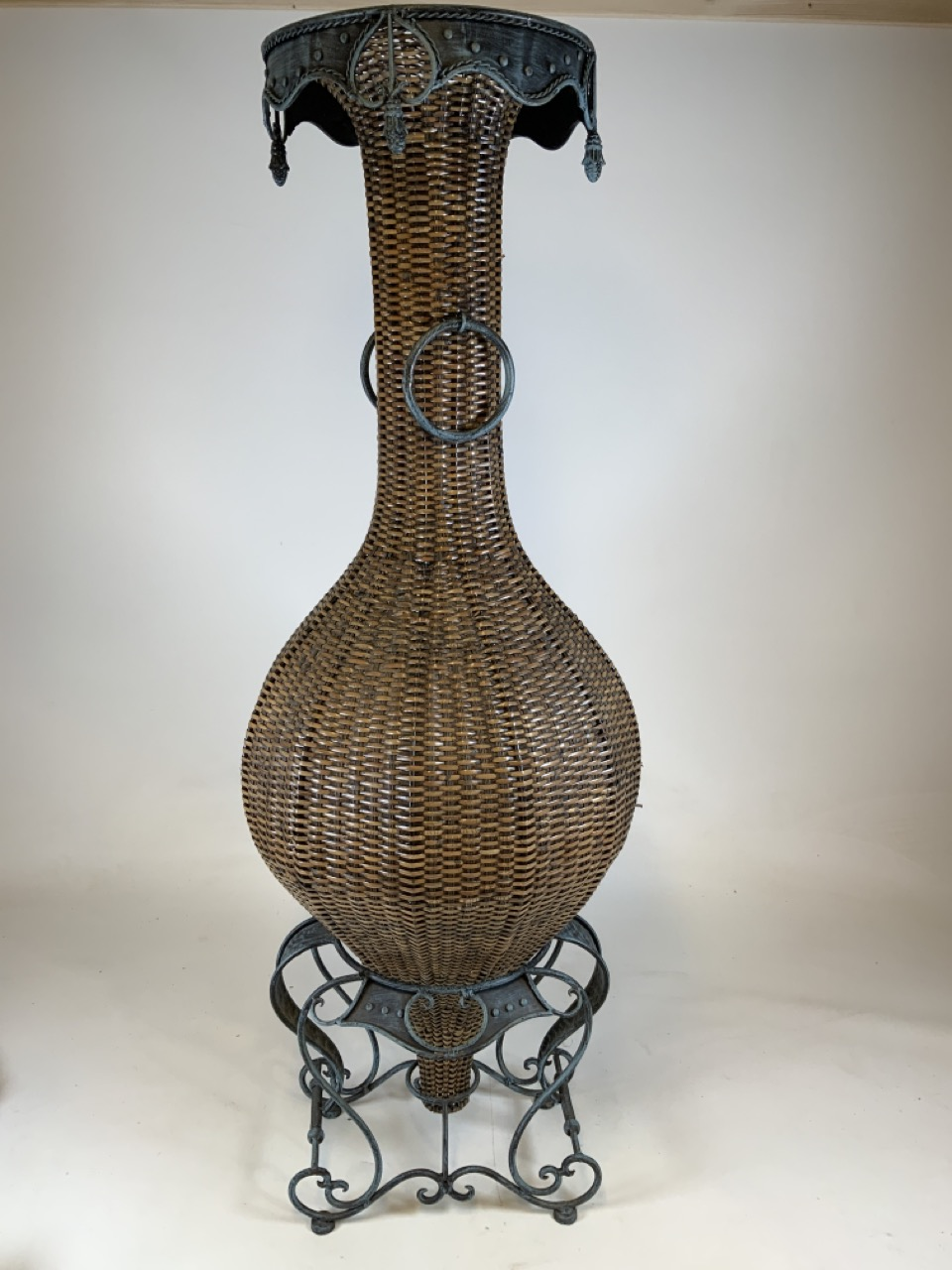 A large wicker conservatory vase in stand with metal hoop handles and decorative metal top. W:24cm x
